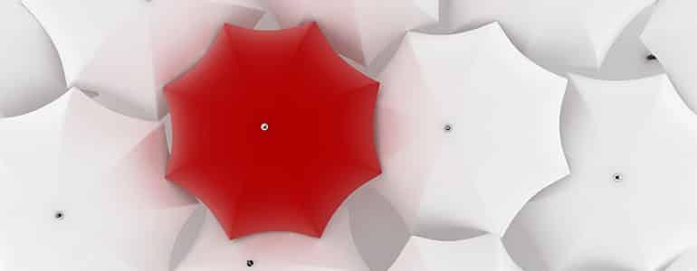 one red umbrella among white umbrellas